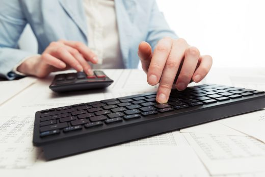 woman using calculator and keyboard - cost of staging a home